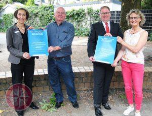 Foto von vier Personen, die ein Plakat zeigen.